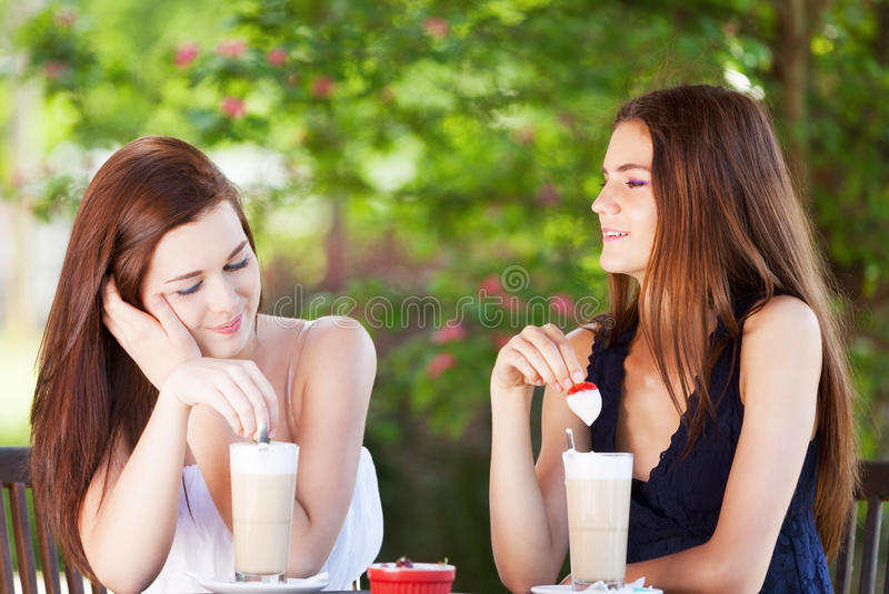 Klatch. Girls chatting in open terrace on lovely sunny day stock image