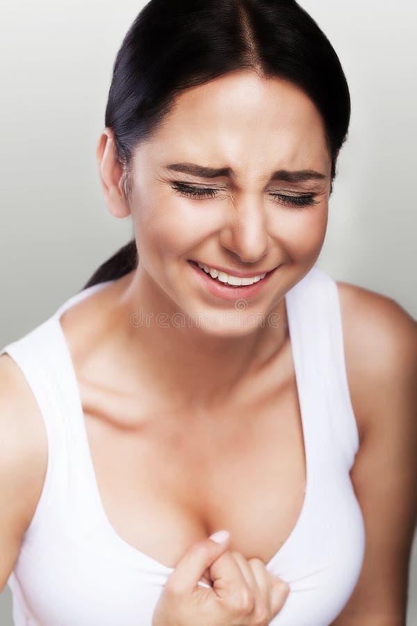 Klatka piersiowa surowy ból Młoda dziewczyna czuje mnóstwo ból w jej sercu Uderzenia Infarct Pojęcie zdrowie na szarym tle obrazy stock