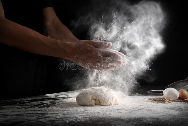Klatschende Hände des Mannes und besprühen Mehl über Teig auf schwarzem Hintergrund stockfoto