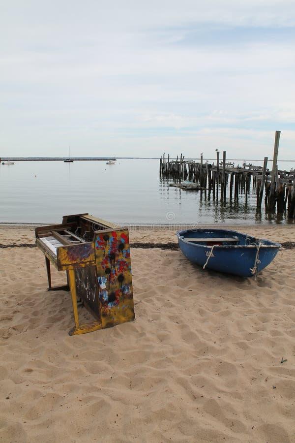 Klavier und Boot auf dem Strand stockbilder