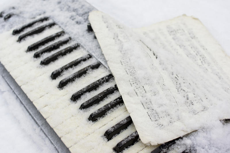 Klavier unter Schnee stockbild