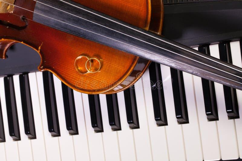 Klaviertastatur, alte Violine und Eheringe stockfotos