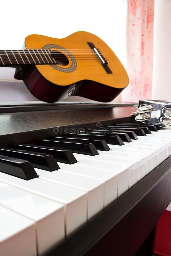 Klaviertastatur mit Gitarre und Tamburin stockbild