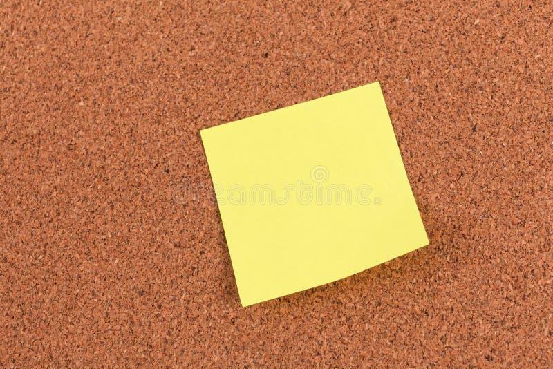 Klebrige Anmerkung der gelben Anzeige über Korkenbrett lizenzfreie stockbilder
