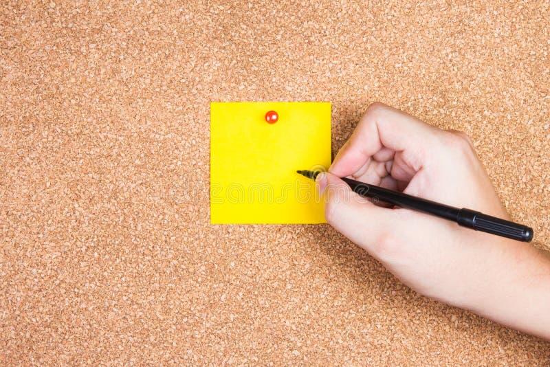 Klebrige Anmerkung der gelben Anzeige über Korkenbrett mit der Hand schreiben zu ihr stockfotos