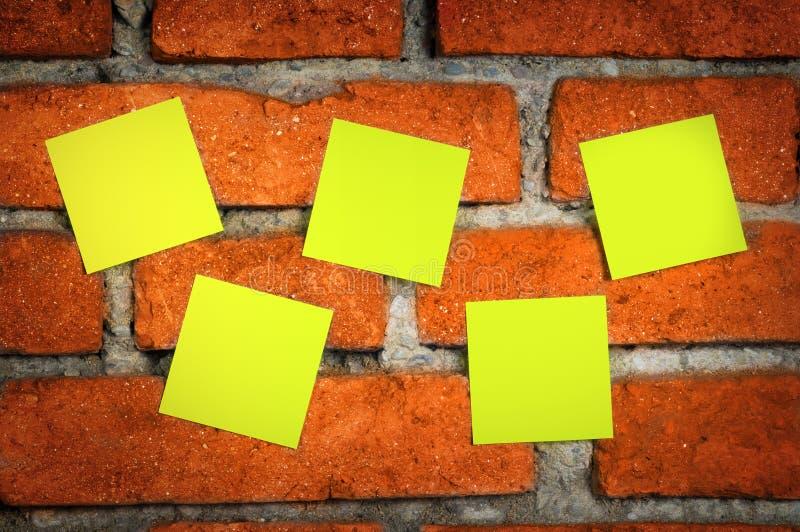 Klebrige Anmerkungen über eine Backsteinmauer lizenzfreie stockfotos