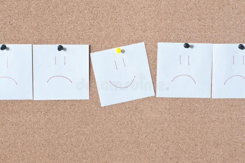 Klebrige Lächelnanmerkung der weißen Anzeige über Korkenbrett stockbild