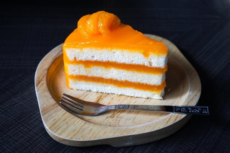 Klebriger orange Kuchen auf hölzerner Platte stockbild