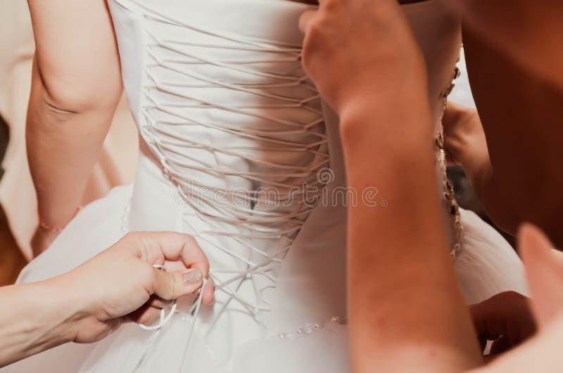 Kledende bruid op huwelijksdag stock afbeelding