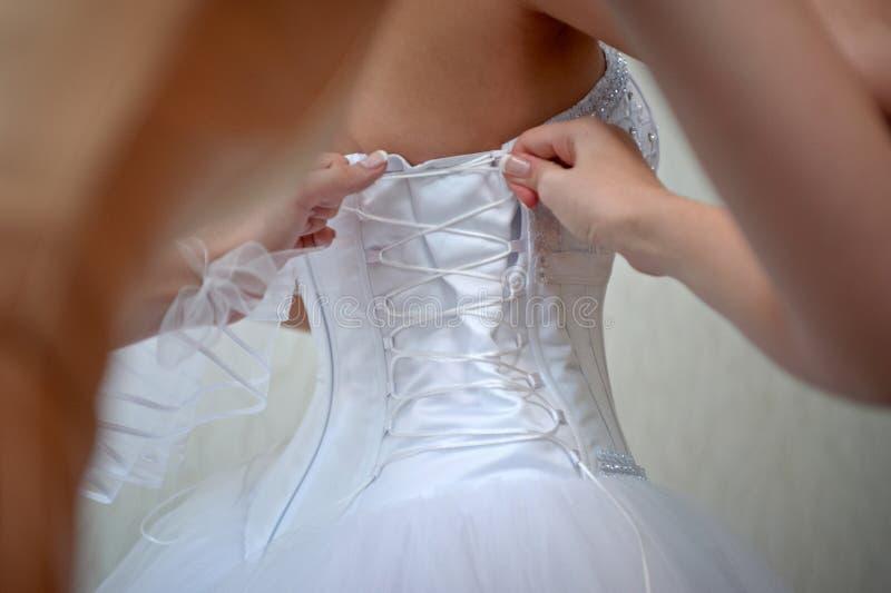 Kledende bruid op huwelijksdag De bruidsmeisjes rijgen bruid Vrouwenhol royalty-vrije stock afbeelding