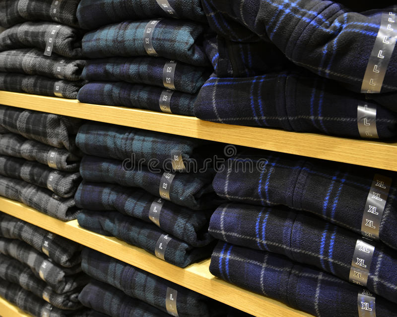 Kleding op de plank in manierwinkel die keurig wordt gestapeld stock foto
