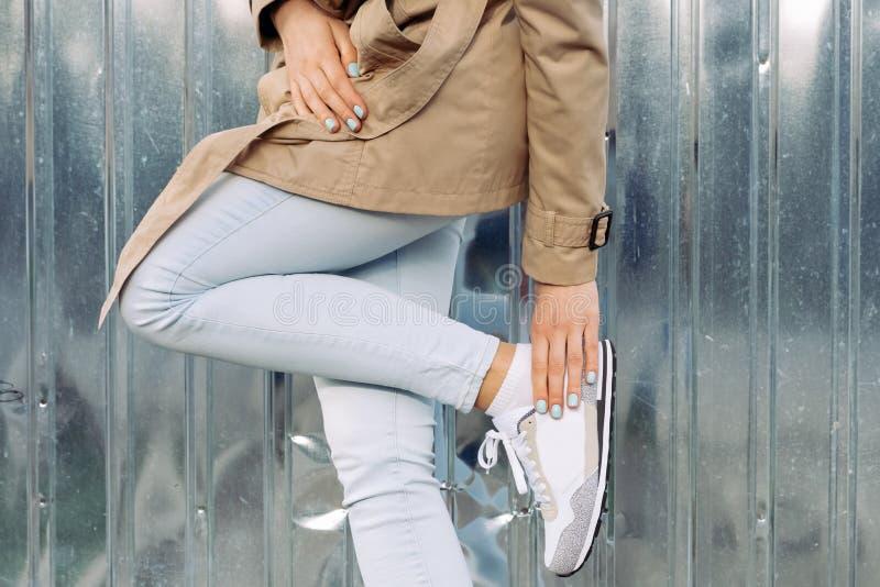 Kledingsdetails: meisje in een beige laag, jeans en tennisschoenen in openlucht stock fotografie