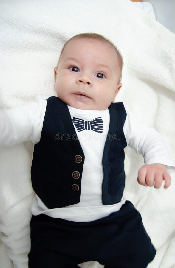 Kleedde de pasgeboren de babyjongen zich van boommaanden oud als zakenman met vlinderdas, gezichtsexpresion stock foto