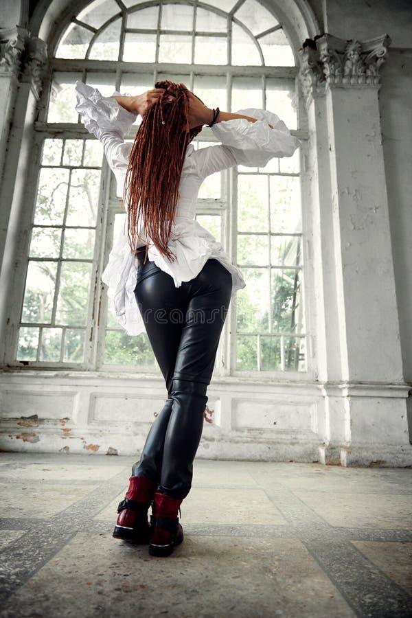 Kleedde het Dreadlocks modieuze meisje zich in wit overhemd en zwarte leerbroeken die in doopvont van oud groot venster stellen,  stock foto's