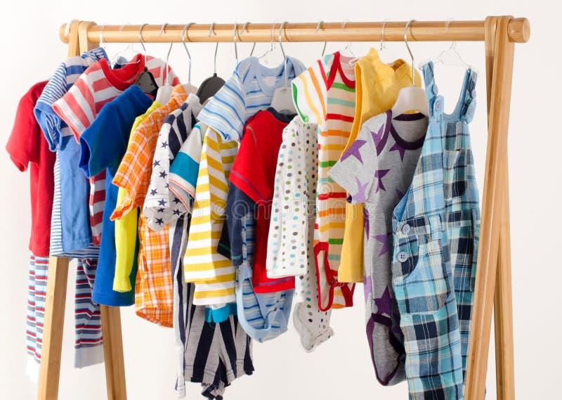 Kleedt kast met kleren op hangers worden geschikt die royalty-vrije stock afbeelding