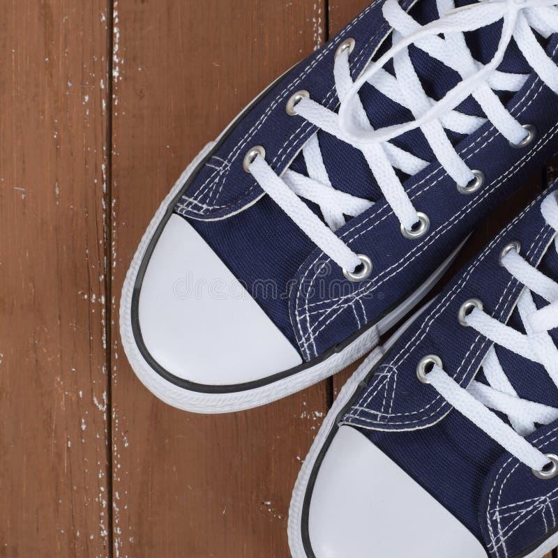 Kleedt schoenen en toebehoren - de hoogste van het paar blauwe gumshoes van het meningsfragment houten achtergrond stock afbeelding