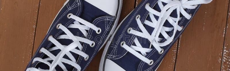 Kleedt schoenen en toebehoren - de hoogste van het paar blauwe gumshoes van het meningsfragment houten achtergrond royalty-vrije stock fotografie