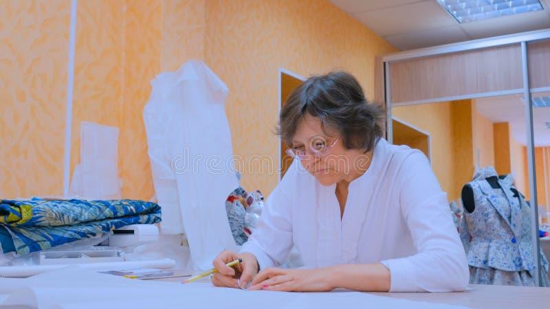 Kleermaker die met patroon van nieuwe kleermakerijeninzameling werken stock afbeelding