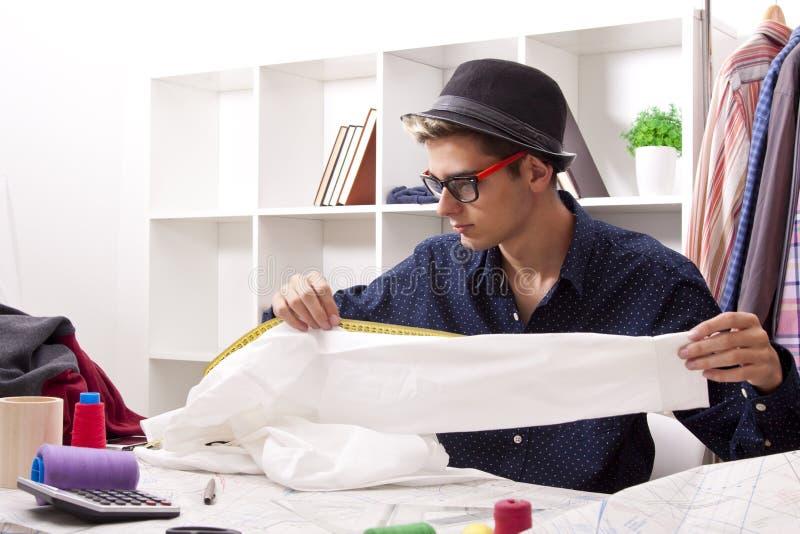 Kleermaker in een textielworkshop stock foto