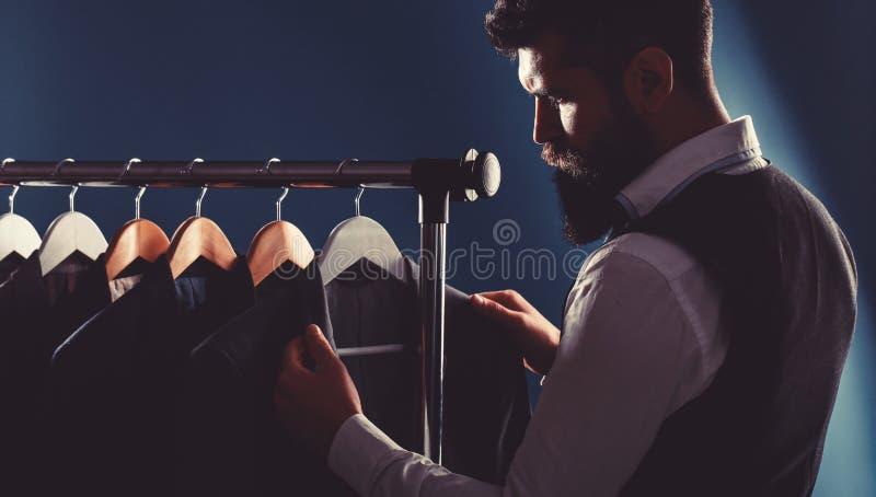 Kleermaker, het maken Het kostuum van mensen, kleermaker in zijn workshop Elegante mensen` s kostuums die op een rij hangen De kl royalty-vrije stock afbeeldingen