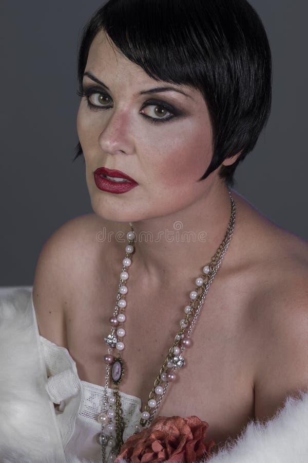Kleermakerijen, de donkerbruine danser van de jaren '20stijl met kort haar en juwelen stock foto's