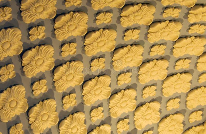 Kleibloemen op de gesneden muur, stock foto