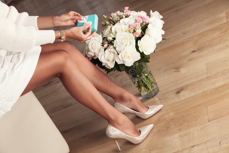 Kleid und hohe Absätze der Frau in Mode, die mit Geschenk sitzen lizenzfreies stockfoto