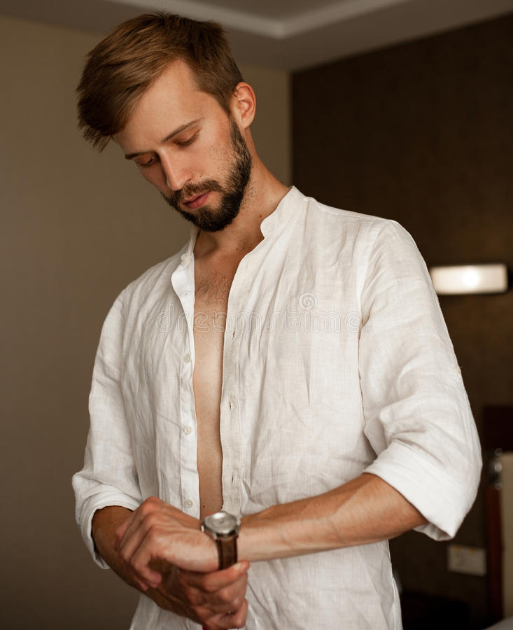 Kleider des jungen Mannes und befestigen Uhrenarmband lizenzfreie stockfotos