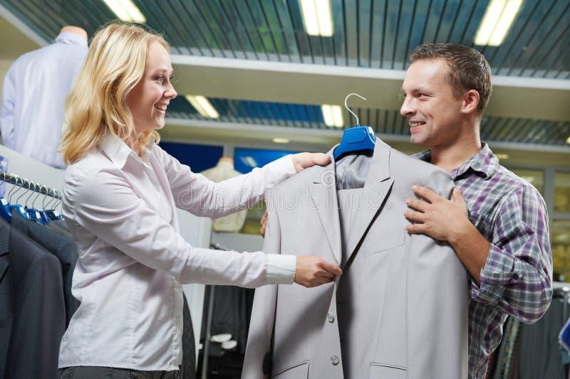 Kleidereinkaufen Verkäufer demonstriert Gesellschaftsanzug zum Mann im Speicher lizenzfreies stockbild