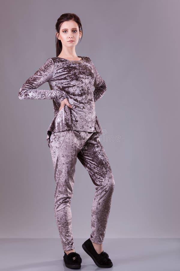 Kleidet silk Samtanzug der Brunettefrauenabnutzung für Geschäftsfrau Büroart über grauem Hintergrund Beiläufiges Mädchen Modekata lizenzfreie stockfotos
