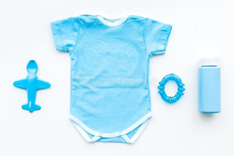 Kleidung des blauen Babys für kleinen Jungen Bodysuit, Spielwaren, Kosmetik auf Draufsicht des weißen Hintergrundes lizenzfreies stockfoto