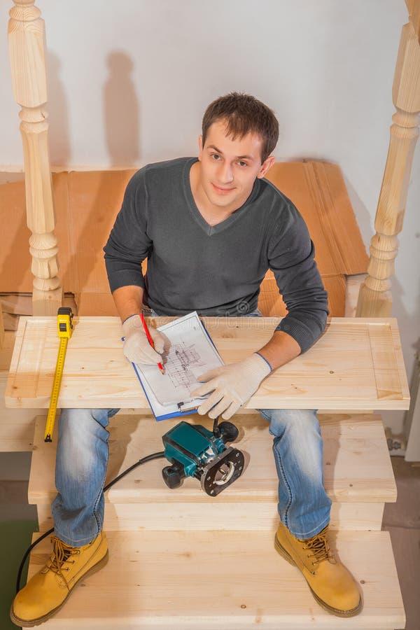 Kleidung einer tragende Funktion des jungen gutaussehenden Mannes, die auf Leiter sitzt   stockfotos