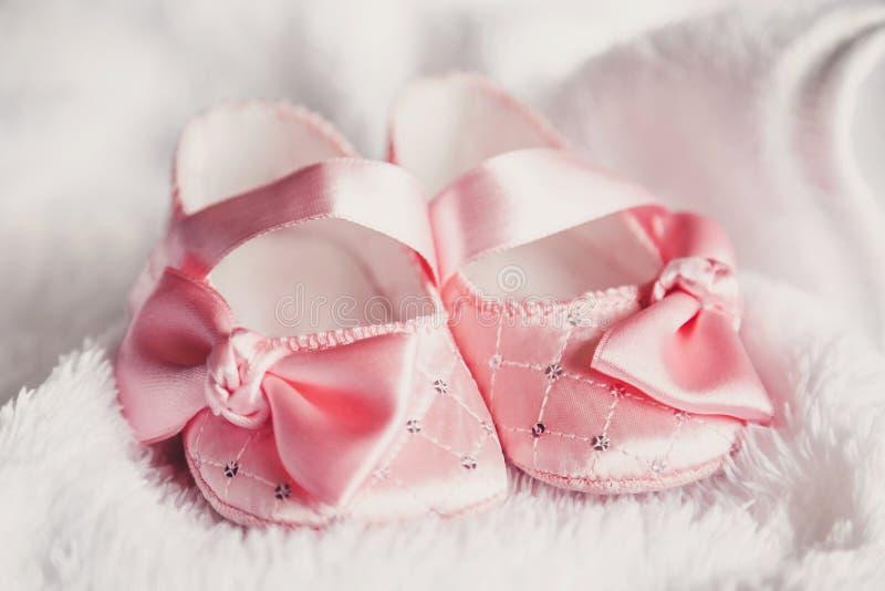 Kleidung für neugeborenes Ein Paar nette Babyrosaschuhe mit einem Bogen für Mädchen auf einem weißen Bett stockfotos