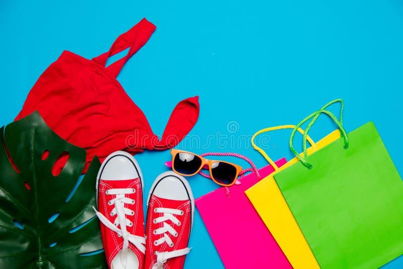 Kleidung, Gummiüberschuhe und Einkaufstaschen mit Palmblatt lizenzfreies stockfoto