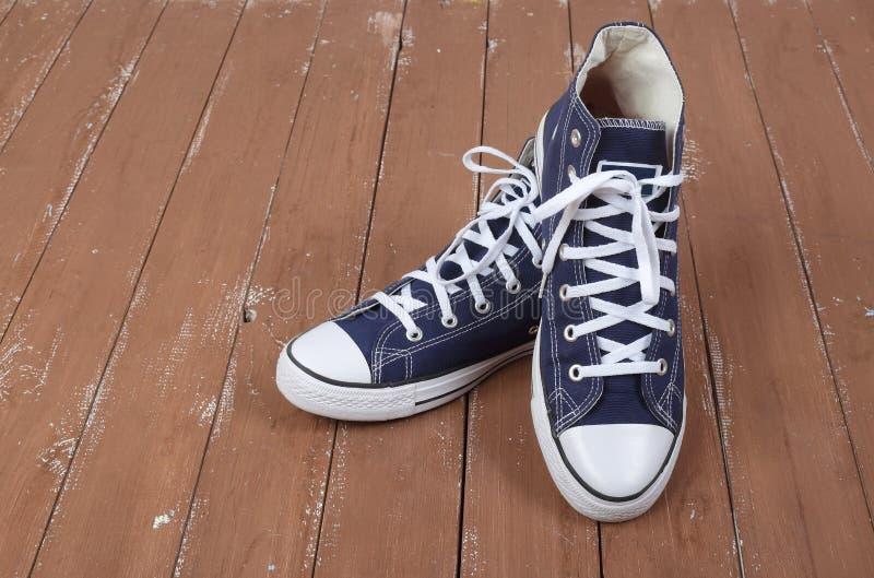 Kleidung, Schuhe und Zubehör - passen Sie blaue Gummiüberschuhe hölzernes backg zusammen stockfotos