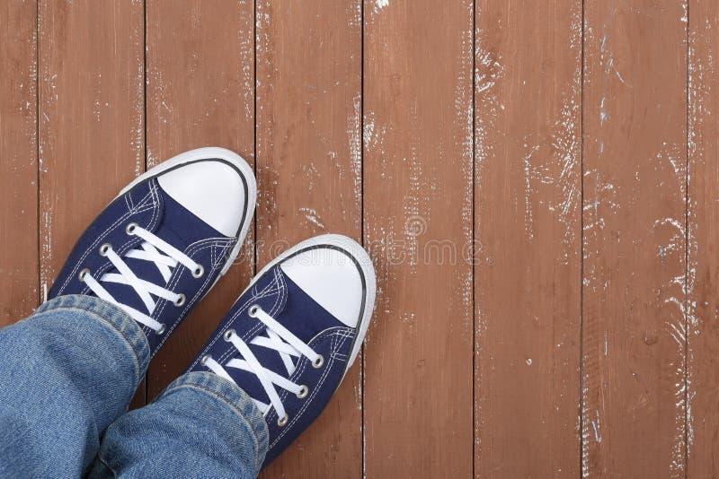 Kleidung, Schuhe und Zusätze - Beine eingesetzt in Gummiüberschuhe und in blaues J lizenzfreies stockbild