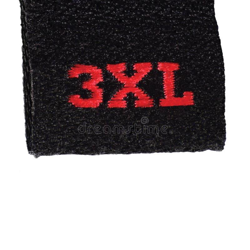 Kleidungs-Aufklebertag der Größe 3XL, schwarzes Gewebe, roter XXXL-Stickereitext, lokalisierte Vertikale, große ausführliche Makr lizenzfreie stockfotos