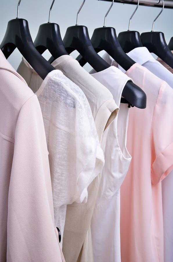 Kleidungs-Pastellfarben der Frauen, die an der Aufhängervertikale hängen lizenzfreie stockfotos