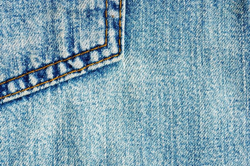 Kleidungseinzelteilblau stonewashed Baumwollgewebebeschaffenheit der verbla?ten Jeans mit N?hten, Verschl?ssen, Kn?pfen und Niete lizenzfreie stockbilder