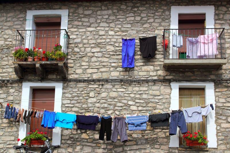 Kleidungzeile, die von den Steinwandhäusern hängt lizenzfreies stockbild