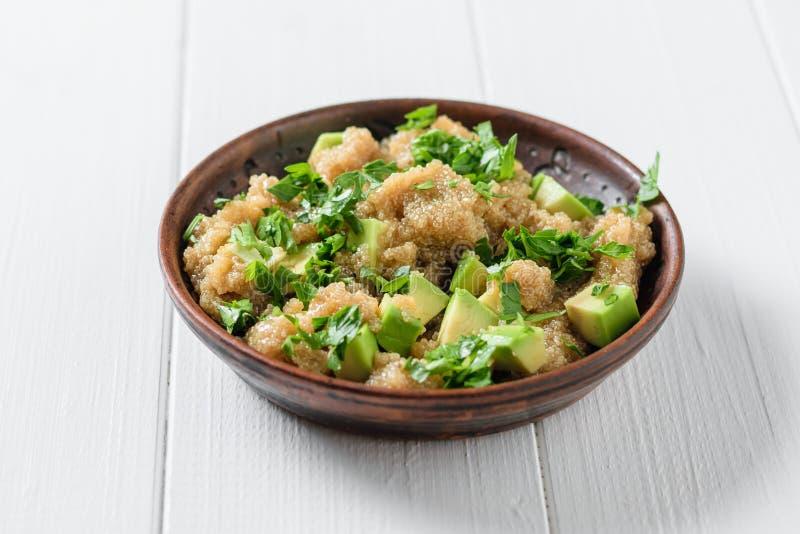 Kleikom met de salade van het amarantzaad met avocadoplakken en peterselie op witte houten lijst royalty-vrije stock afbeelding