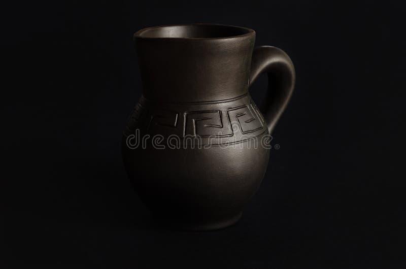 Kleikruik, oude ceramische vaas op zwarte achtergrond stock fotografie