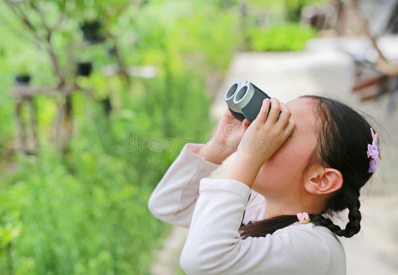 Klein Aziatisch kindmeisje dat in de lucht door de verrekijkers in het natuurveld in de openlucht kijkt Ontdek en avontuur stock fotografie
