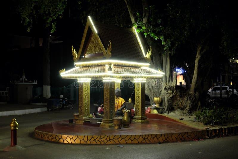 Klein Boeddhistisch die heiligdom met decoratieve lichten wordt versierd Het standbeeld van Boedha gekleed in geel royalty-vrije stock foto's