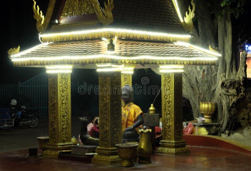 Klein Boeddhistisch die heiligdom met decoratieve lichten wordt versierd Het standbeeld van Boedha gekleed in geel stock foto
