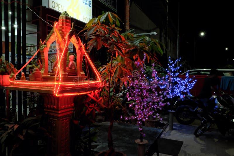 Klein Boeddhistisch die heiligdom met lichten wordt versierd Kunstmatige installaties op de nachtstraat stock afbeelding