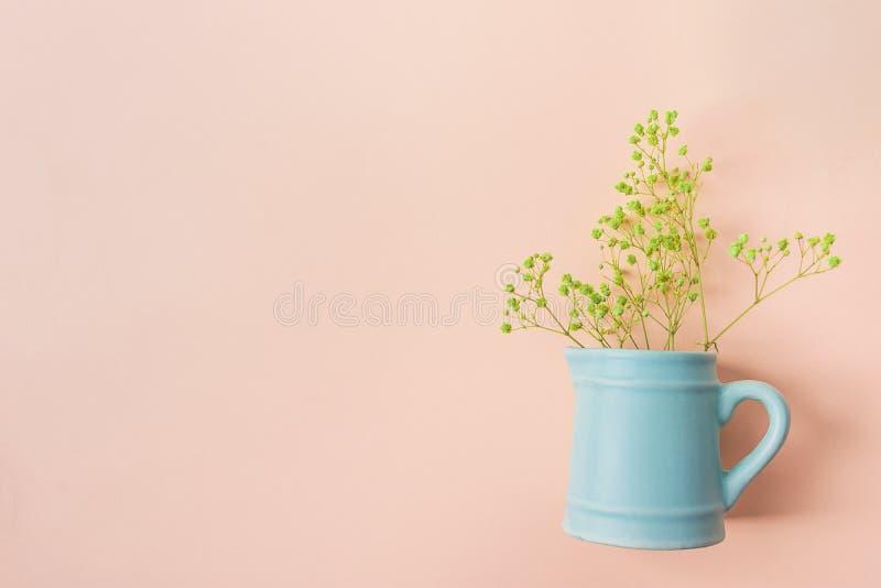 Klein Boeket van Gele Acaciabloemen in Uitstekende Ceramische Blauwe Kruik op Roze Achtergrond Vlak leg Creatief Het Malplaatje v stock foto