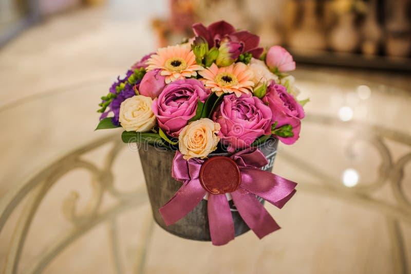 Klein boeket van roze en purpere bloemen in doos royalty-vrije stock foto