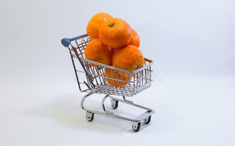 Klein boodschappenwagentje met vele clementines stock foto's