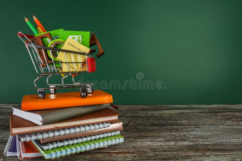 Klein boodschappenwagentje met verschillende schoolkantoorbehoeften en notitieboekjes op lijst tegen kleurenachtergrond royalty-vrije stock afbeelding